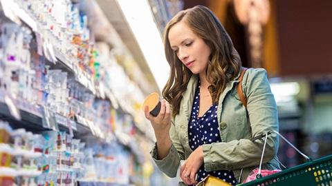 Une femme lit l'étiquette d'un yaourt dans un magasin.
