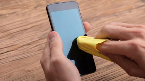 Un smartphone est en train d'être nettoyé avec une chiffonette pour écran.