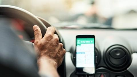 Smartphone sur un support dans une voiture avec l'app Google Map ouverte.