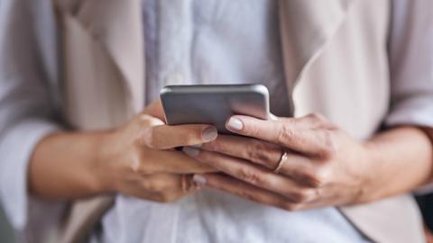 Iphone dans les mains d'une personne qui tente de gérer le stockage de ses données.