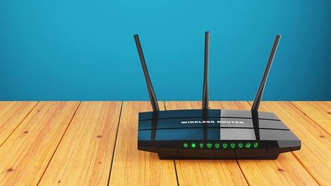 Un router internet posé sur une table en bois devant un mur peint en bleu.