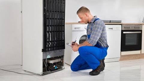 Réfrigérateur vu de dos, en train d'être réparé.